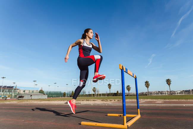 Сильная молодая женщина в спортивной одежде перепрыгивает через препятствие на голубое небо во время тренировки на стадионе — стоковое фото
