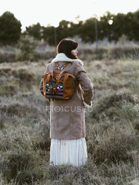 Woman in warm jacket and trendy backpack standing outdoors in daylight — Stock Photo