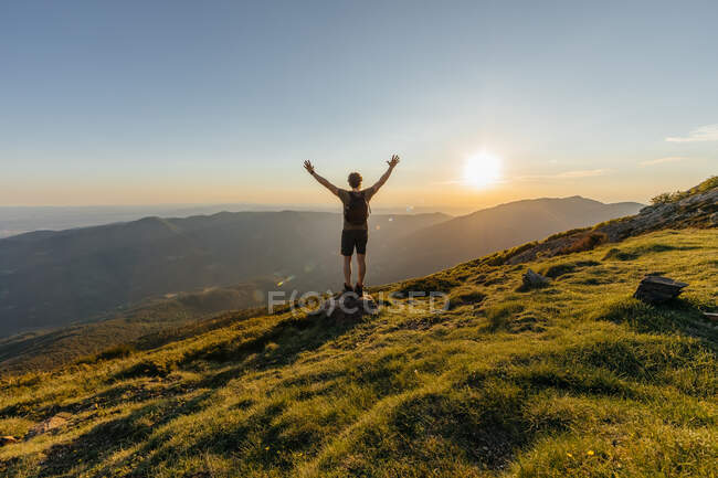 Back view of young man with back pack contemplating amazing mountain landscape on the countryside — Stock Photo