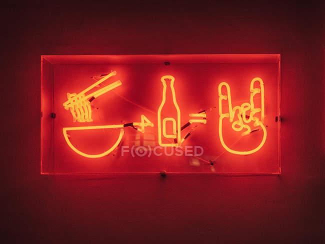 Letrero iluminado de restaurante asiático que ofrece comida y bebida colgando en la pared - foto de stock