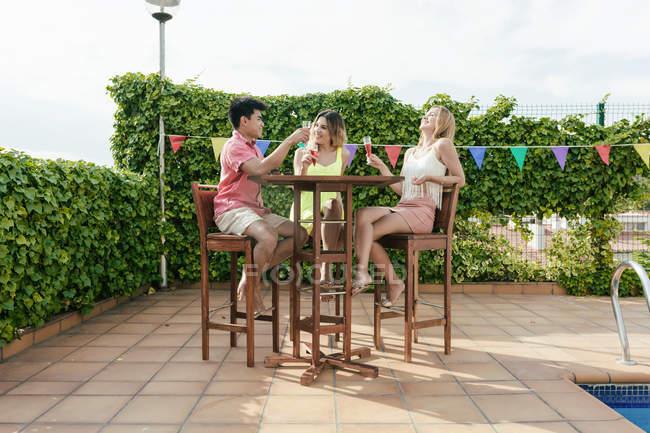 В солнечный день компания друзей пьет сэндвич на террасе бара — стоковое фото