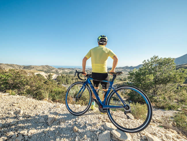 Healthy man resting and enjoying view with bicycle on mountain road in a sunny day — Stock Photo