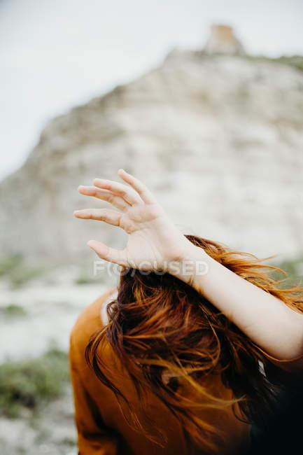 Mulher anônima segurando a mão acima da cabeça no fundo da paisagem selvagem deserto — Fotografia de Stock