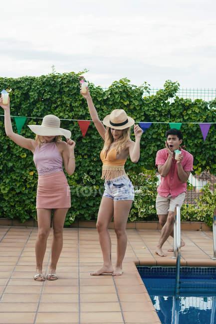 Группа друзей во время вечеринки у бассейна, танцуют, смеются и пьют коктейли — стоковое фото