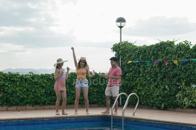 Gruppo di amici che hanno una festa in piscina mentre ballano, ridono e bevono cocktail — Foto stock