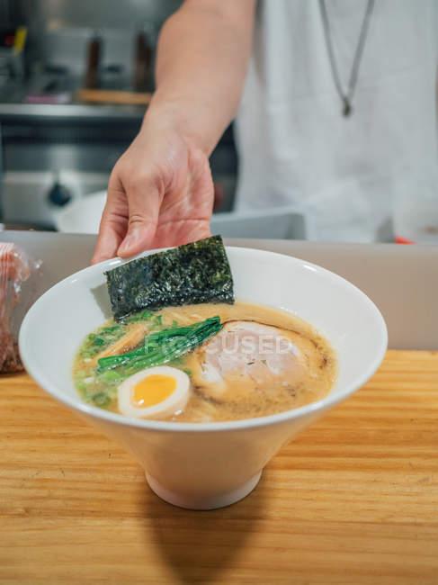 Рука человека положить миску свежеприготовленных традиционных японских блюд на деревянный счетчик в ресторане — стоковое фото