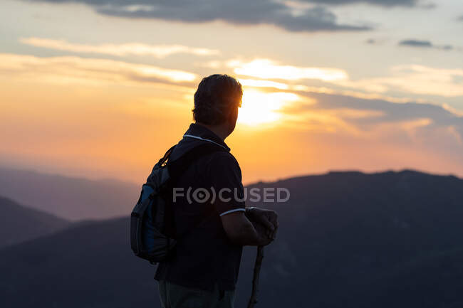 Silhouette of back view of a senior man with back pack and wooden stick hiking contemplating amazing mountain landscape — Stock Photo