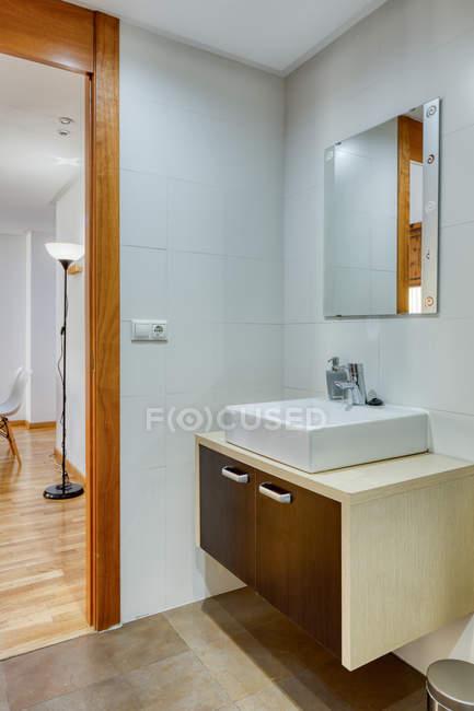 Interno del bagno in stile minimalista moderno con specchio e lavandino su supporto in legno — Foto stock