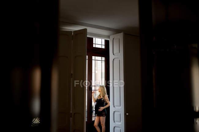 Mujer embarazada reflexiva en lencería de pie cerca de la puerta abierta en casa - foto de stock