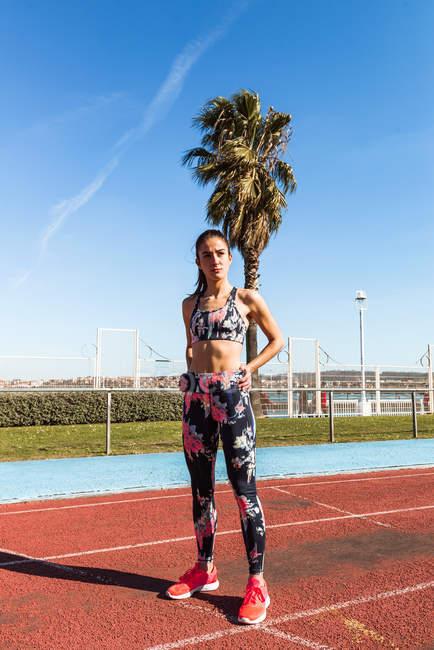 Стройная молодая женщина в спортивной одежде смотрит в сторону, стоя на поле на стадионе во время тренировки — стоковое фото