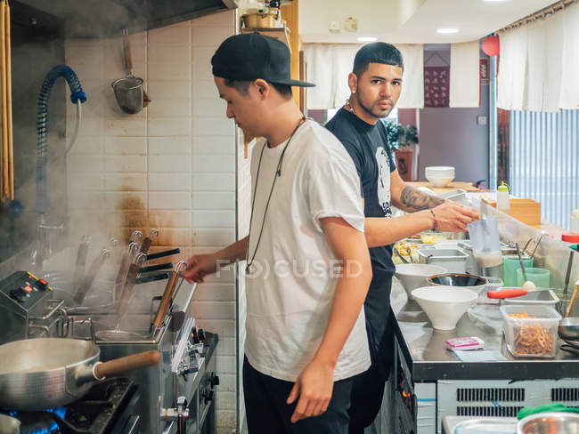 Side view of multiracial young men cooking Japanese dish called ramen in Asian restaurant and looking in camera — Stock Photo