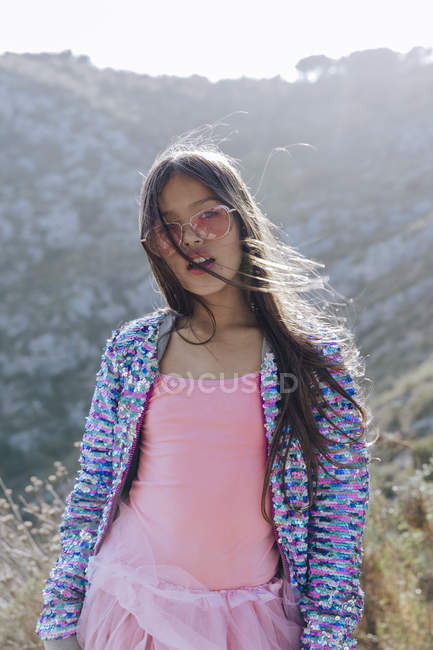 Long haired cute girl in pink sunglasses and sweater with sequins on background of mountain in sunlight — Stockfoto