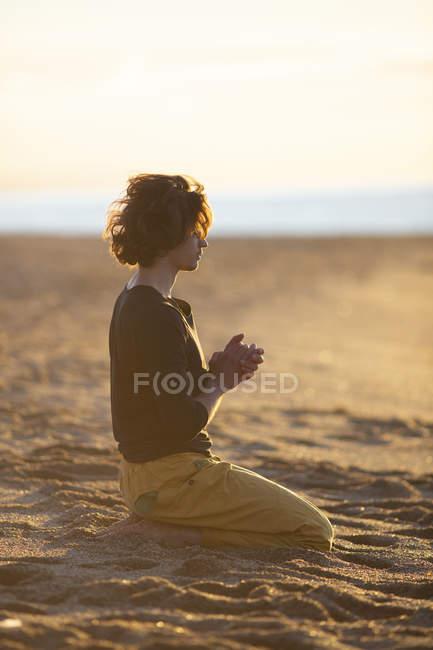Вдумлива людина з закритими очима і руками в молитві жест сидить на колінах на піщаному пляжі в сонячному світлі — стокове фото