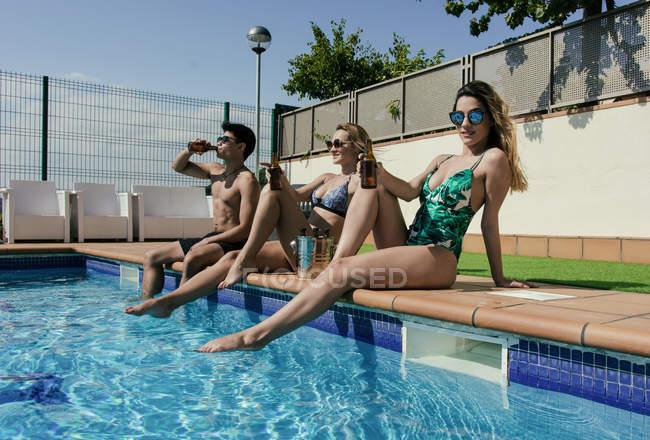 Gruppo di amici prendere il sole a bordo piscina mentre bevono birra in una giornata estiva — Foto stock