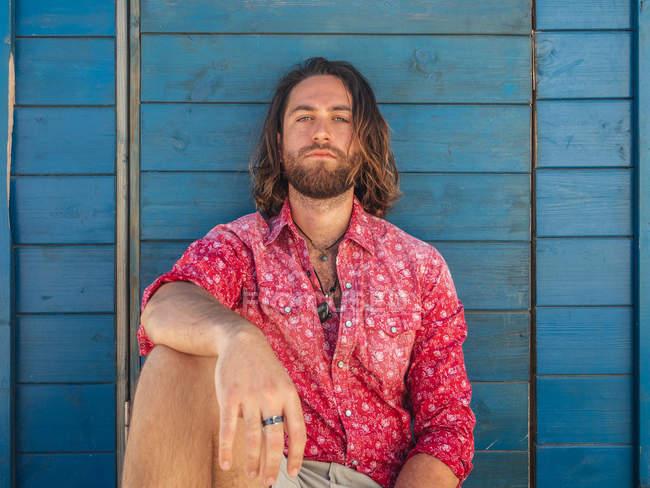 Selbstbewusster bärtiger Mann in lässigem Outfit sitzt vor blauer Wand im Resort — Stockfoto