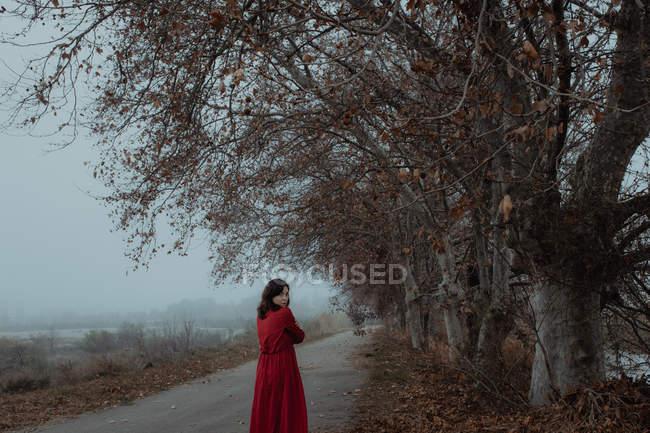 Mujer de ensueño en vestido rojo caminando por el camino vacío de terreno misterioso haze - foto de stock