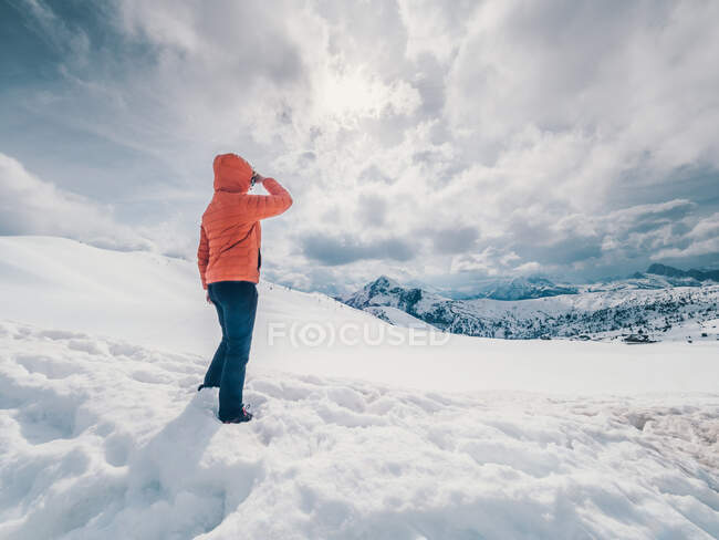 Unrecognizable person standing in snow surrounded by forest and mountains — Stock Photo