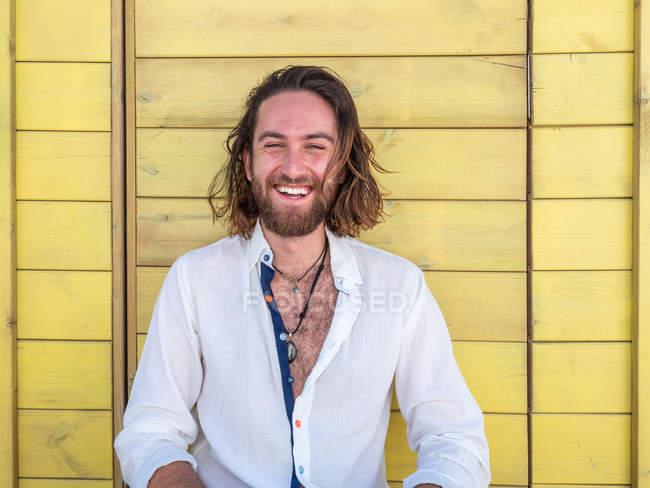 Смеющийся бородатый мужчина в повседневной одежде позирует против желтой стены на курорте — стоковое фото