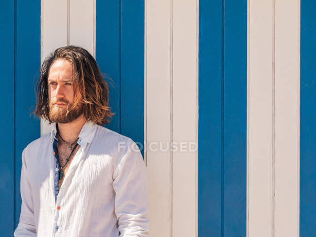 Впевнена бородатий людина в повсякденний одяг постановки проти синьо-білої стіни — стокове фото