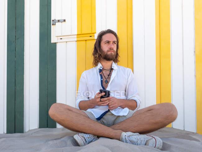 Бородатый мужчина в повседневной одежде держит смартфон, сидя на песке напротив полосатой стены на курорте — стоковое фото