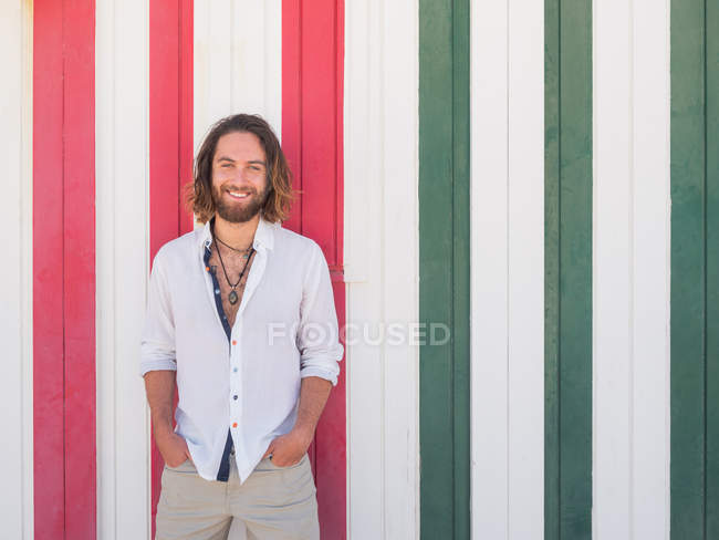 Smiling bearded man in casual outfit standing against striped wall on resort — Stock Photo