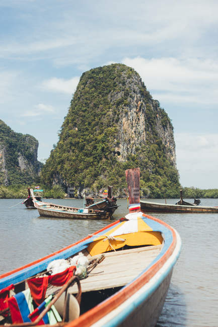 Wooden boats floating on peaceful water of lagoon with green rock on background, Thailand — Stock Photo