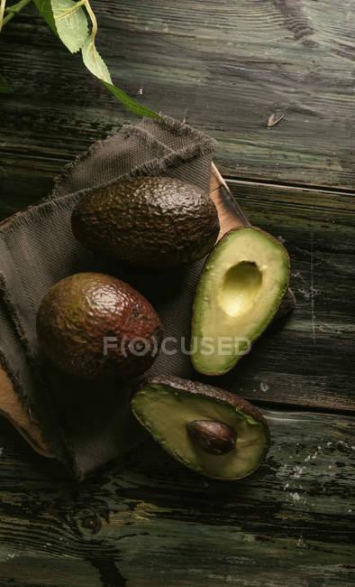 Fresh whole and halved avocados on wooden table — Stock Photo