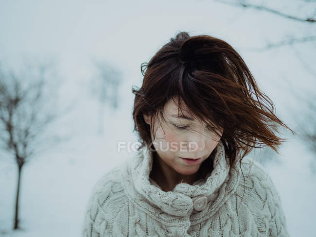 Portrait of pensive attractive brunette in white sweater on background of snowy area — Stock Photo