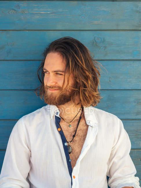 Homme barbu de sourire dans la tenue occasionnelle regardant loin contre le mur bleu sur la ressource — Photo de stock