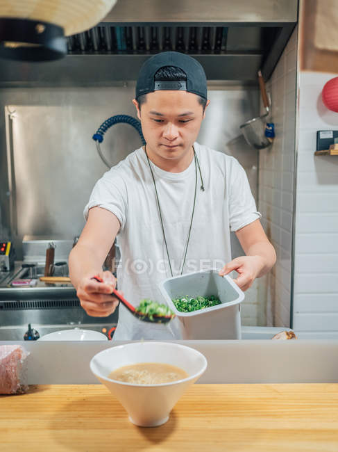 Asian male adding chopped green onions in bowl with fresh cooked Japanese dish on wooden table — Stock Photo