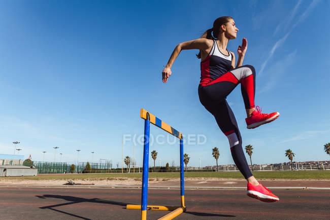 Сильна молода жінка в спортивному одязі стрибали над перешкодою проти синього неба під час тренування на стадіоні — стокове фото