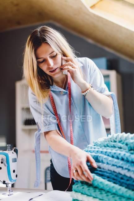 Mujer concentrada smiling smiling y tocando montones de tela blanda mientras que tiene una conversación satelital en atelier erótico. - foto de stock