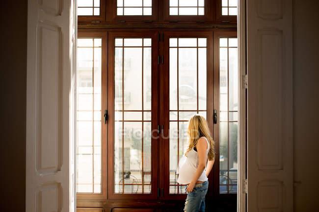 Вдумлива вагітна жінка в повсякденний одяг стоячи біля вікна будинку — стокове фото