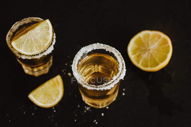 Coups de tequila traditionnels servis avec des morceaux de lime fraîche et de sel sur table noire — Photo de stock