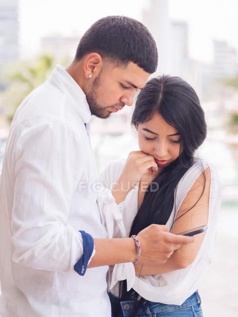 Молодая привлекательная пара в белой одежде пишет смс на мобильный телефон — стоковое фото