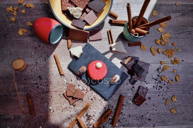 De cima da tábua de ardósia com mousse de framboesa na mesa entre ingredientes bagunçados com chocolate e paus de canela — Fotografia de Stock