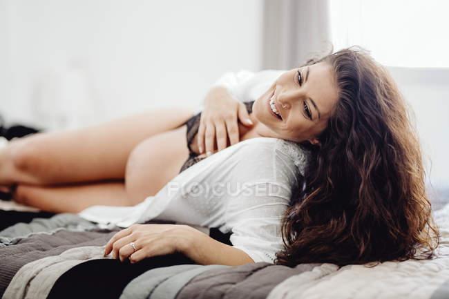 Mulher gravida feliz no roupa interior que encontra-se na cama — Fotografia de Stock