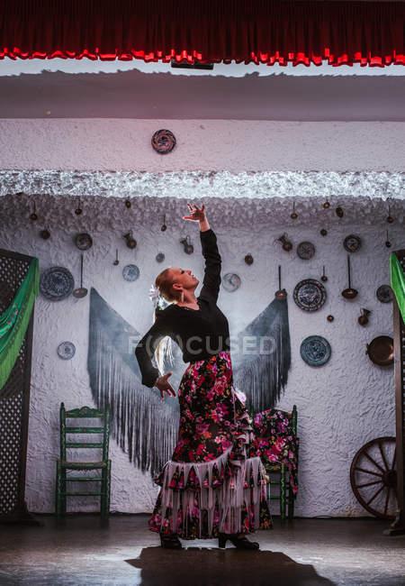 Ballerina in costume da flamenco in piedi in posizione di danza in camera etnica con oggetti antichi sulla parete — Foto stock