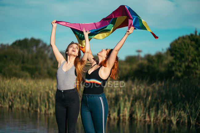 Cheerful women with LGBT flag in nature — Stock Photo