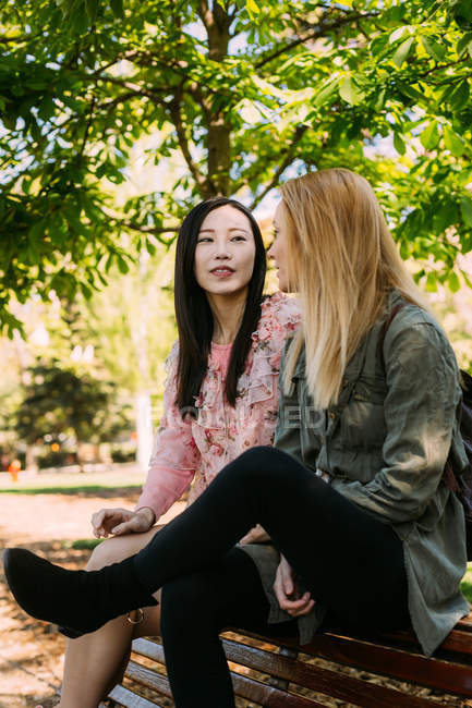 Two multiracial young women in casual outfits talking and looking at each other while sitting on bench in park — Stock Photo