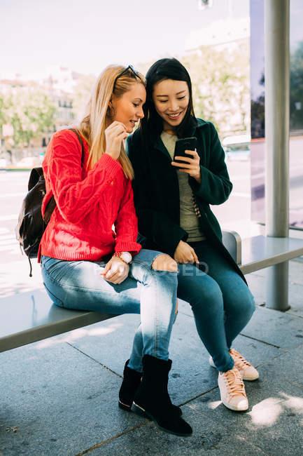 Молоді багаторасові жінки дивляться смартфон, сидячи на автобусній зупинці разом. — стокове фото