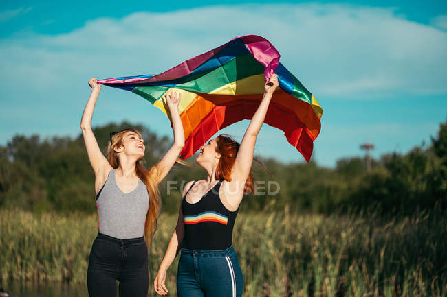 Happy lesbians holding and waving rainbow flag, laughing while standing on blurred background of field together — Stock Photo