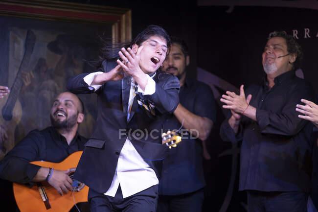 Чоловік у чорному вбранні танцює фламенко біля латиноамериканських музикантів під час виступу проти малювання на темній сцені. — стокове фото