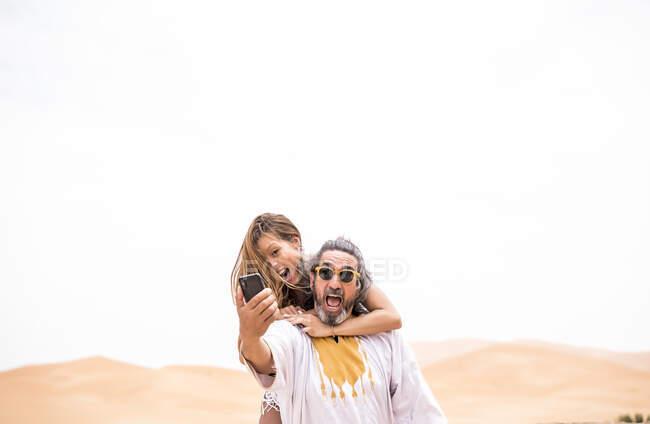 Homme d'âge moyen avec une femme tirant son selfie expressivement sur la terrasse contre le désert sablonneux, Maroc — Photo de stock