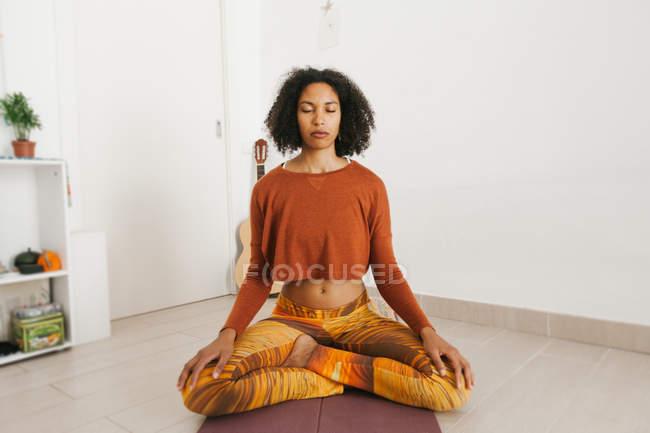 Афроамериканка привлекательная молодая женщина сидит в позе йоги со скрещенными ногами и медитирует с закрытыми глазами дома — стоковое фото