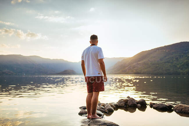 Back view of man standing on rock in water looking at mountains in sunset light — Stock Photo