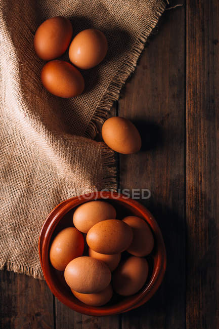 Ovos de galinha com tigela e saco em mesa de madeira — Fotografia de Stock