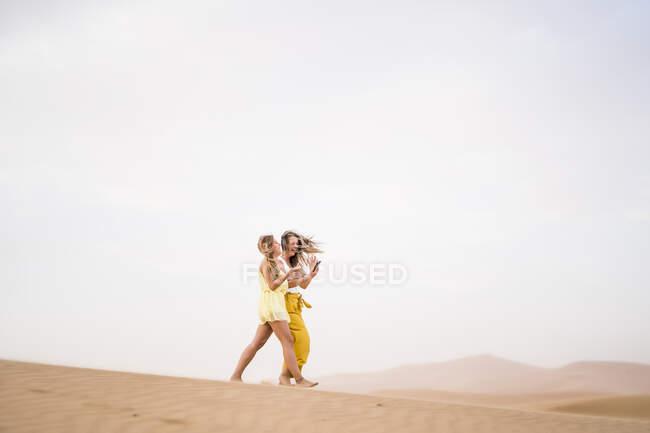 Веселий стиль двох блондинок, які використовують мобільний телефон у пустелі Марокко. — стокове фото