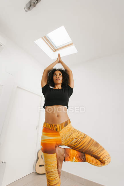 African American attractive young woman performing yoga posture with stretched arms on mat in light room — Stock Photo