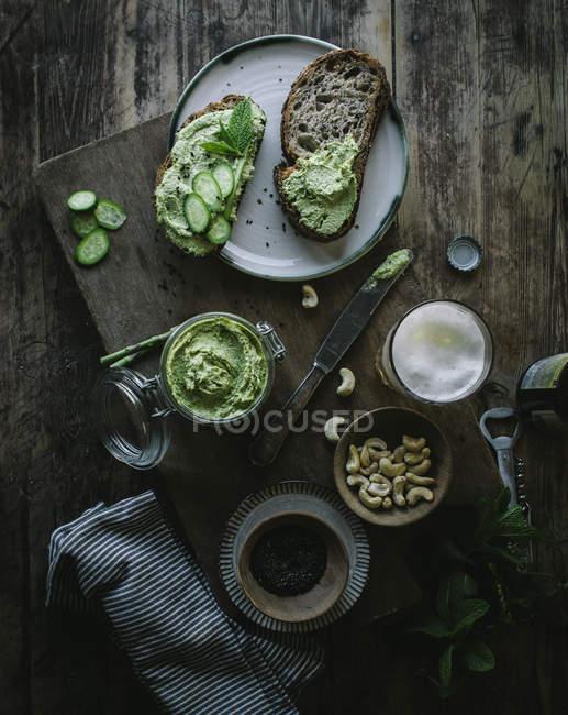 Сверху тосты с зеленым кешью паштет и ломтики огурца с пивом, банкой и орехами на деревянном столе — стоковое фото